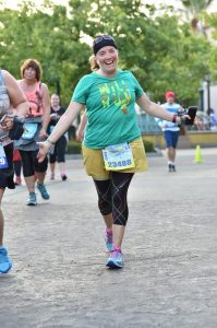 A woman runs accross a race finish line smiling