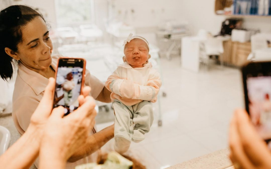 People taking photos of newborn baby with phones. Credit Jonathan Borba, Unsplash